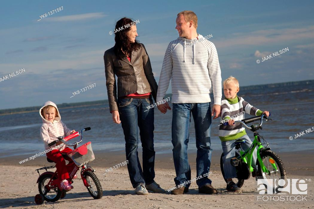 Stock Photo: Happy Young Family Holding Hands Walking with Kids on Bicycles by Sea, Pärnu Beach, Estonia.
