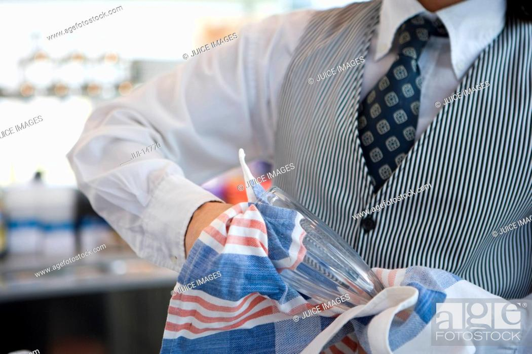 Stock Photo: Waiter drying glass, mid section.