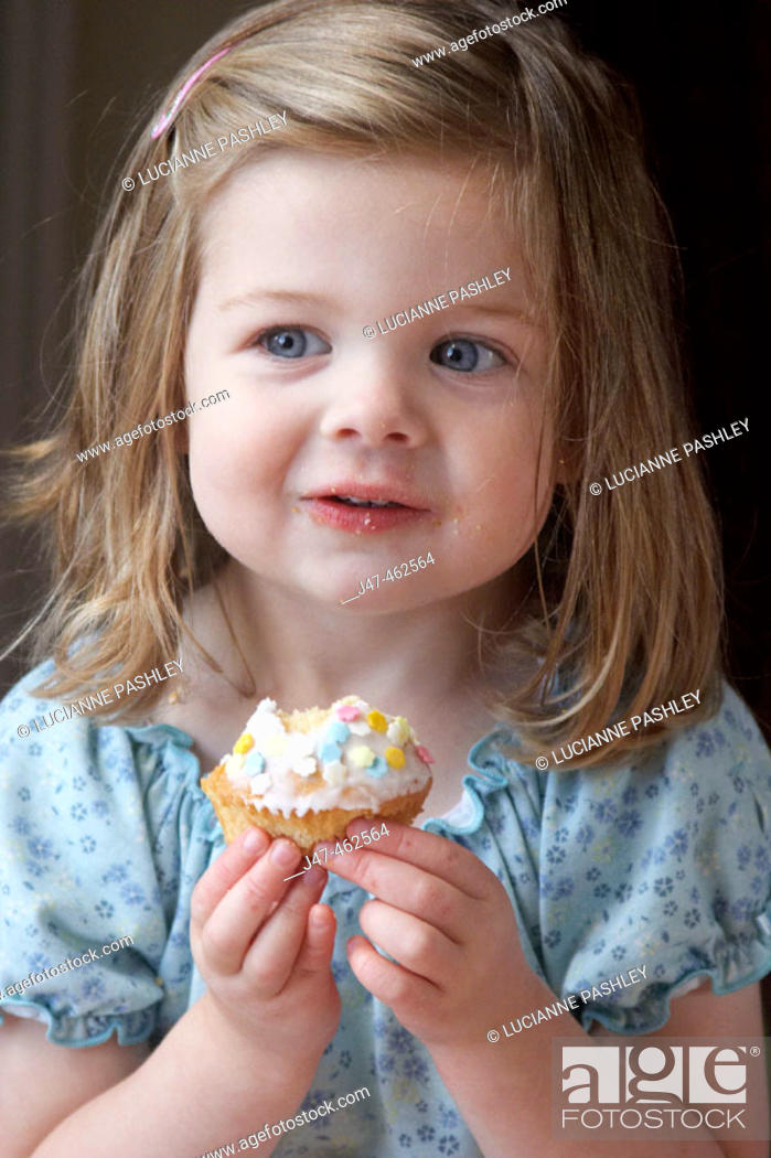 Stock Photo: Little girl's third birthday party, eating a bun, smiling.