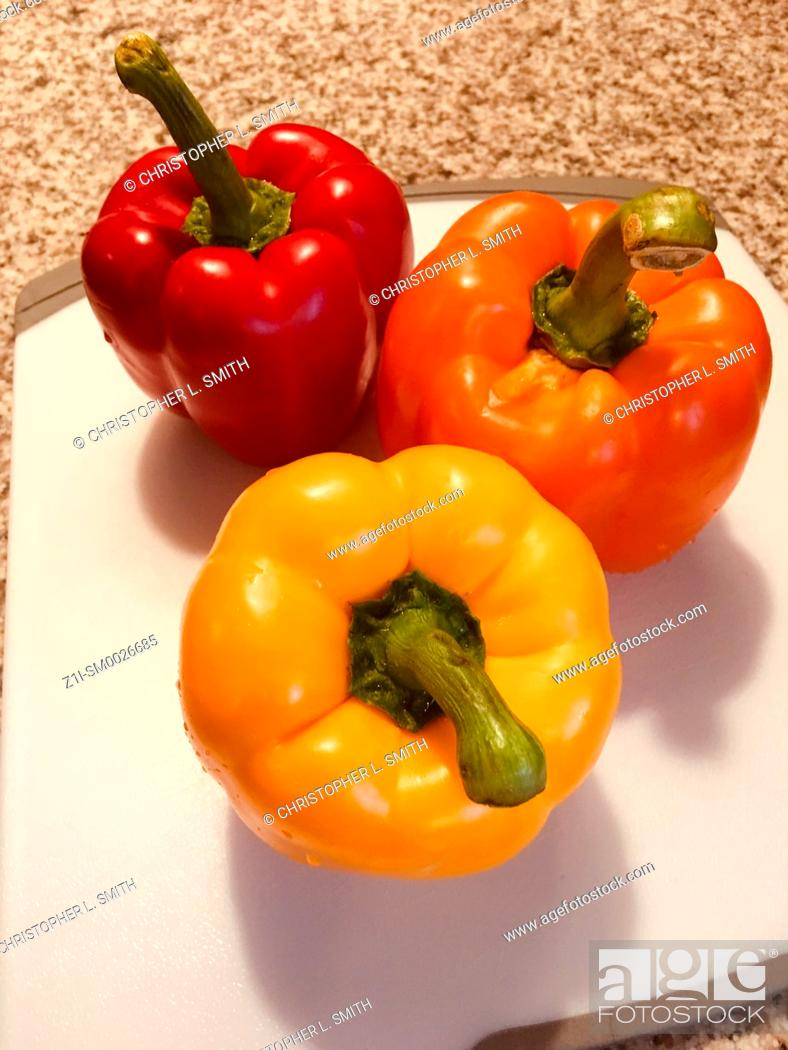 Stock Photo: Fresh perfect Red, Yellow and Orange peppers on a cutting board in a kitchen.