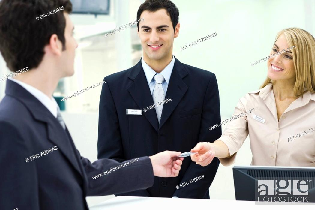 Stock Photo: Man giving credit card to smiling customer service representatives.