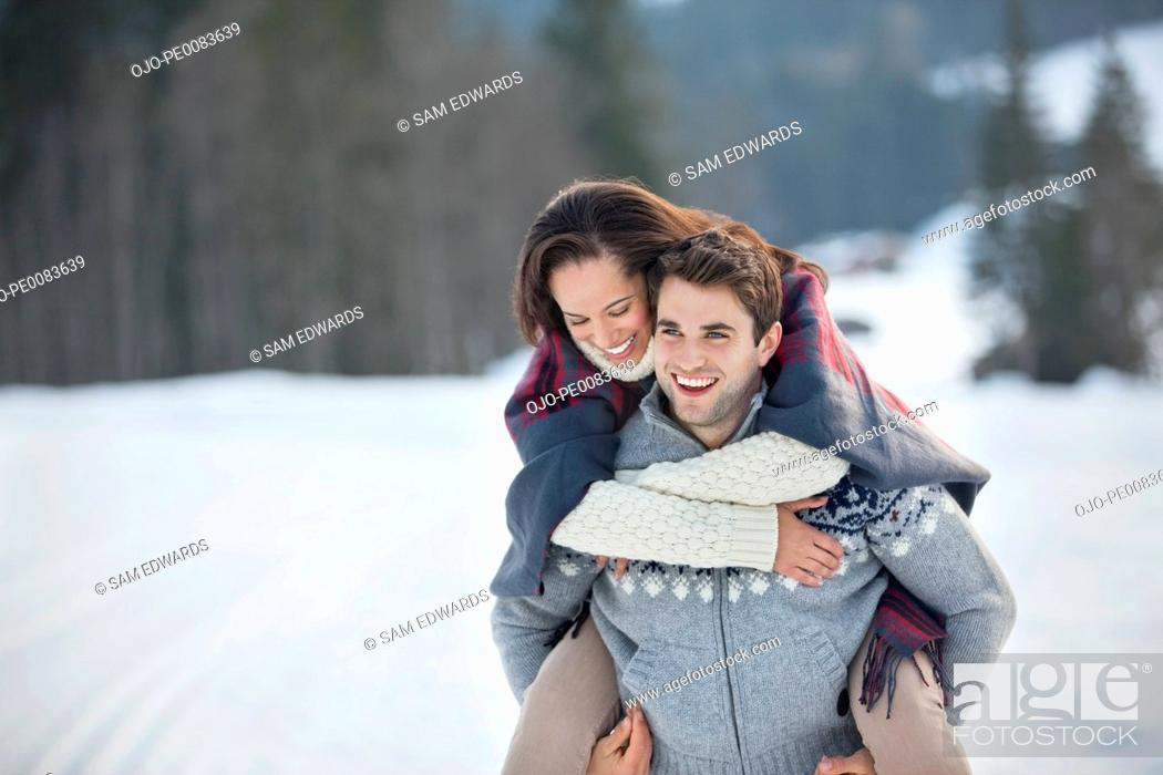 Stock Photo: Man piggybacking woman in snow.