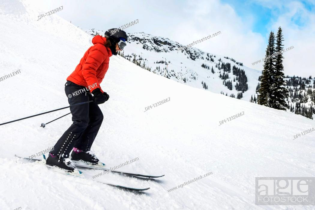 Photo de stock: A downhill skier in a red coat skiing on the snow covered Rocky Mountains; Whistler, British Columbia, Canada.