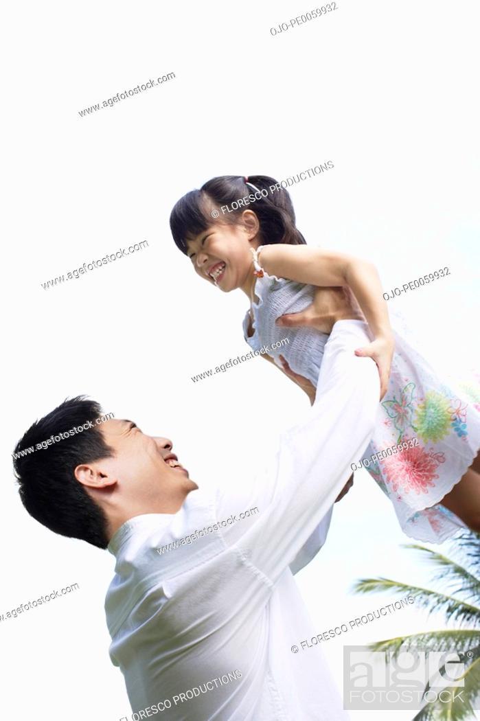 Stock Photo: Man lifting up young girl outdoors.