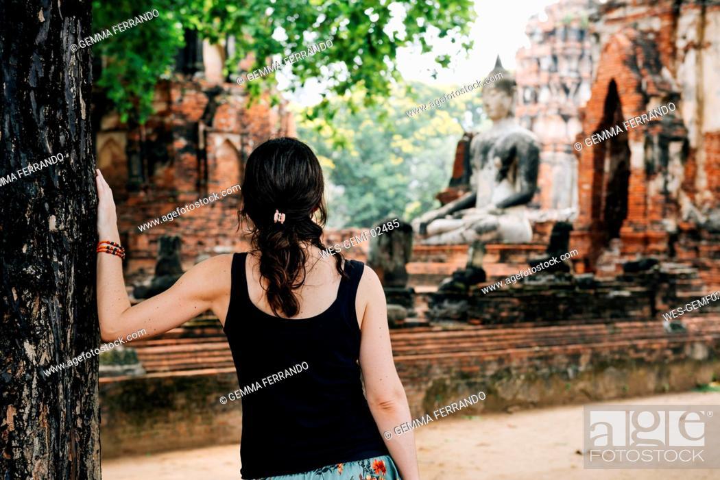 Stock Photo: Thailand, Ayutthaya, Woman looking at a Buddha statue at Wat Mahathat.