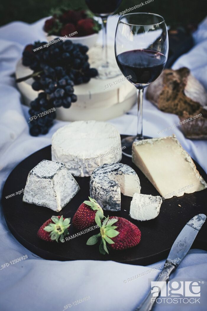 Stock Photo: A cheese platter with strawberries and red wine on a picnic blanket.