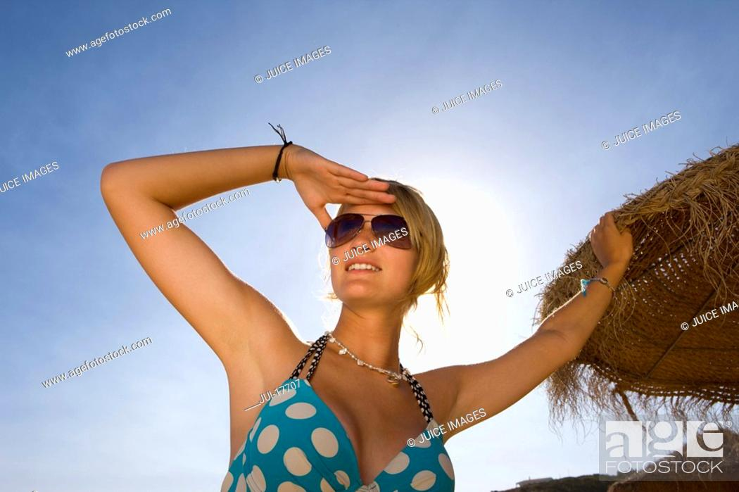 Stock Photo: Teenage girl posing by beach umbrella.