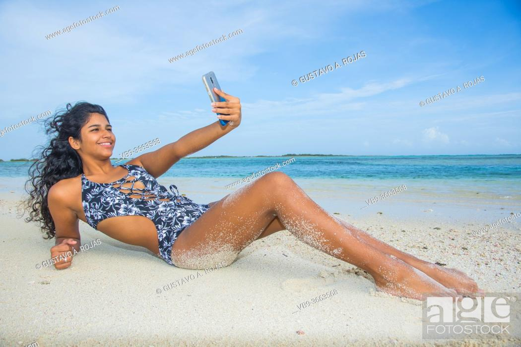 Stock Photo: Young black woman taking a selfie at beach.