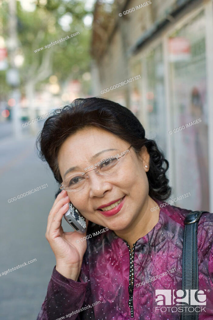 Stock Photo: Middle-aged woman talking on her cell phone.