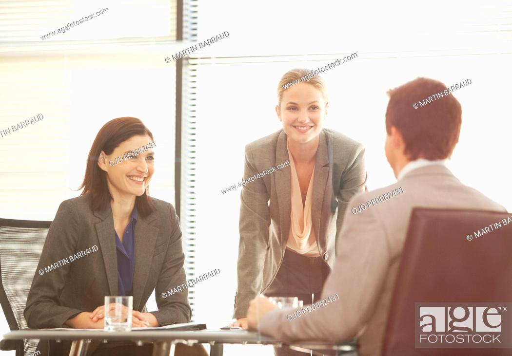 Stock Photo: Smiling business people meeting in office.