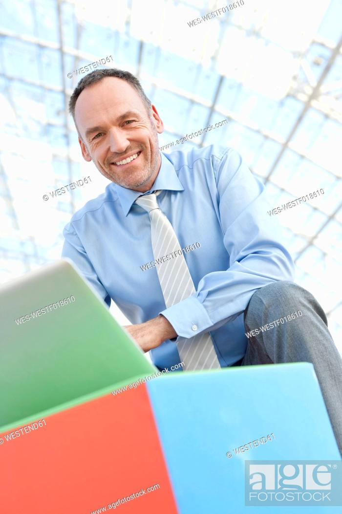 Stock Photo: Germany, Leipzig, Businessman using laptop with cubes, portrait.