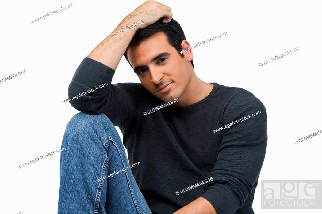 Stock Photo: Portrait of a young man sitting with his hand in his hair.