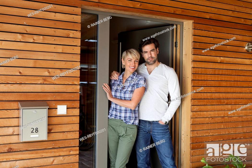 Stock Photo: Germany, Bavaria, Nuremberg, Mature couple standing at front door of house.