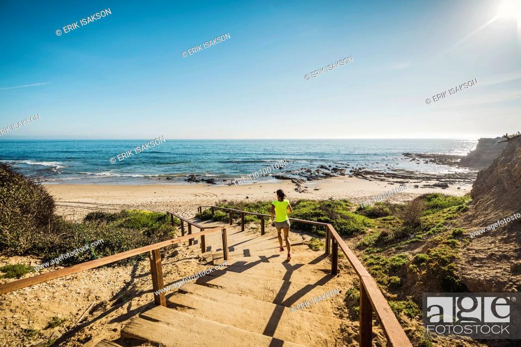 Stock Photo: USA, California, Newport Beach, Woman running down stairs.