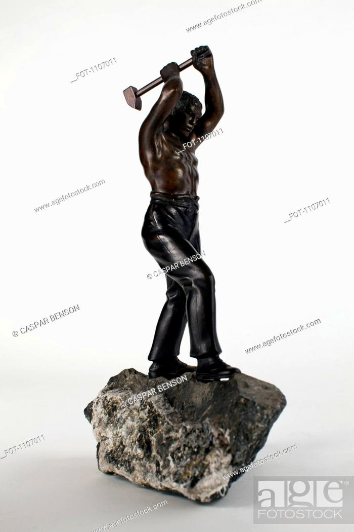 Stock Photo: Statue of a manual worker swinging a sledgehammer.