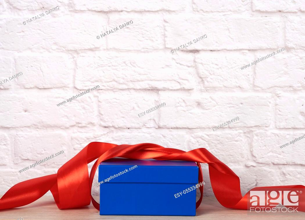 Stock Photo: blue cardboard box with gift and red silk ribbon on white brick wall background.