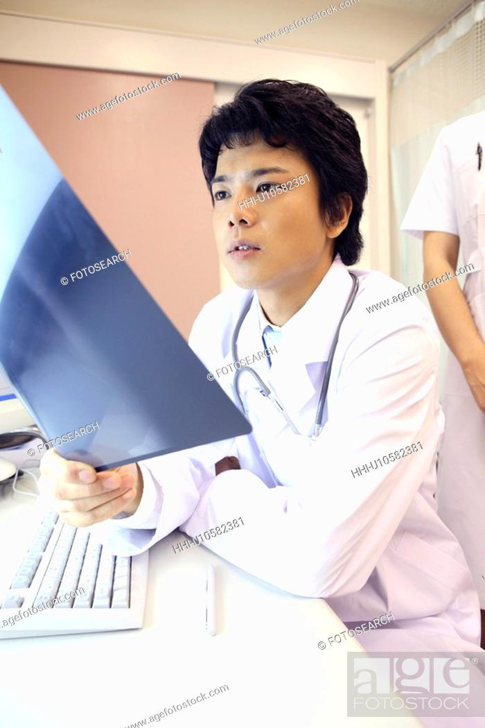 Stock Photo: Doctor looking at X-ray.