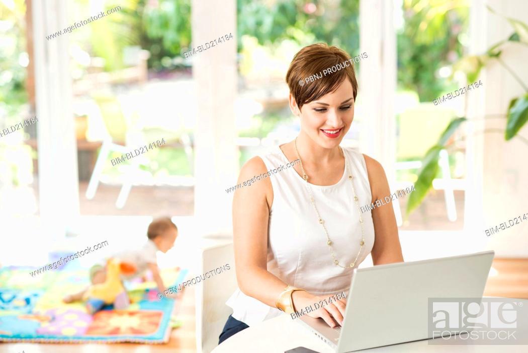 Photo de stock: Caucasian mother using laptop at counter.