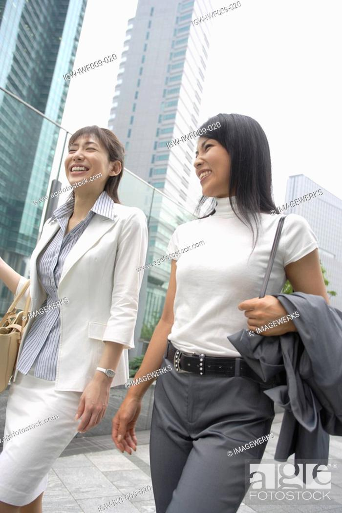 Stock Photo: Two women laughing as they walk beside the glass railing.