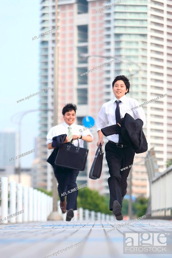 Stock Photo: Young Japanese businessmen running on the street.