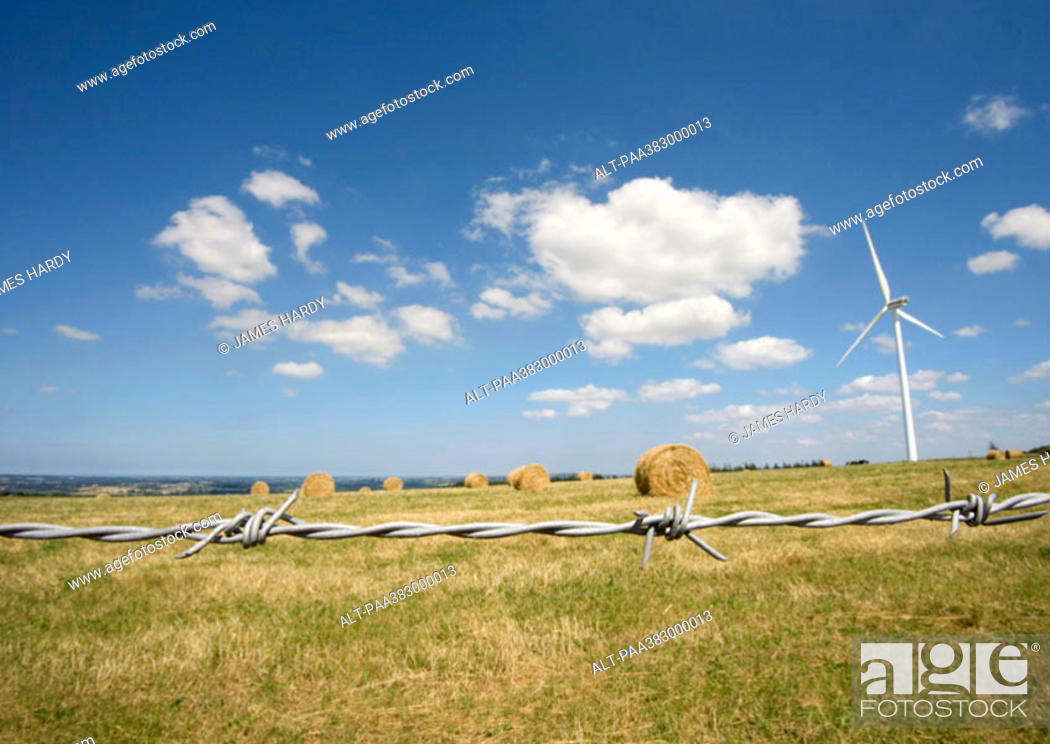 Stock Photo: Wind turbine in field with bales of hay, barbed wire in foreground.