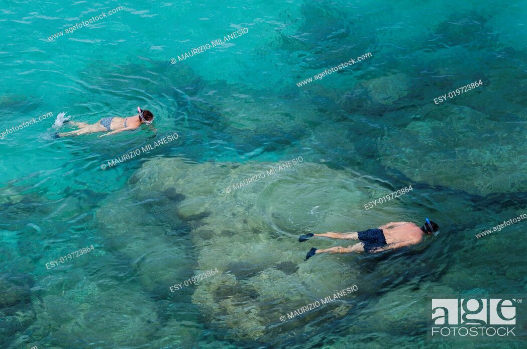 Stock Photo: Two people do snorkeling near the rocks in a wonderful blue and green sea.