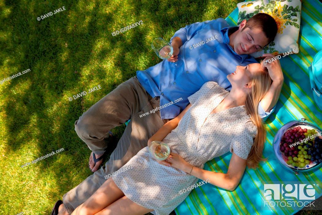 Stock Photo: Young couple lying on picnic blanket, overhead view.