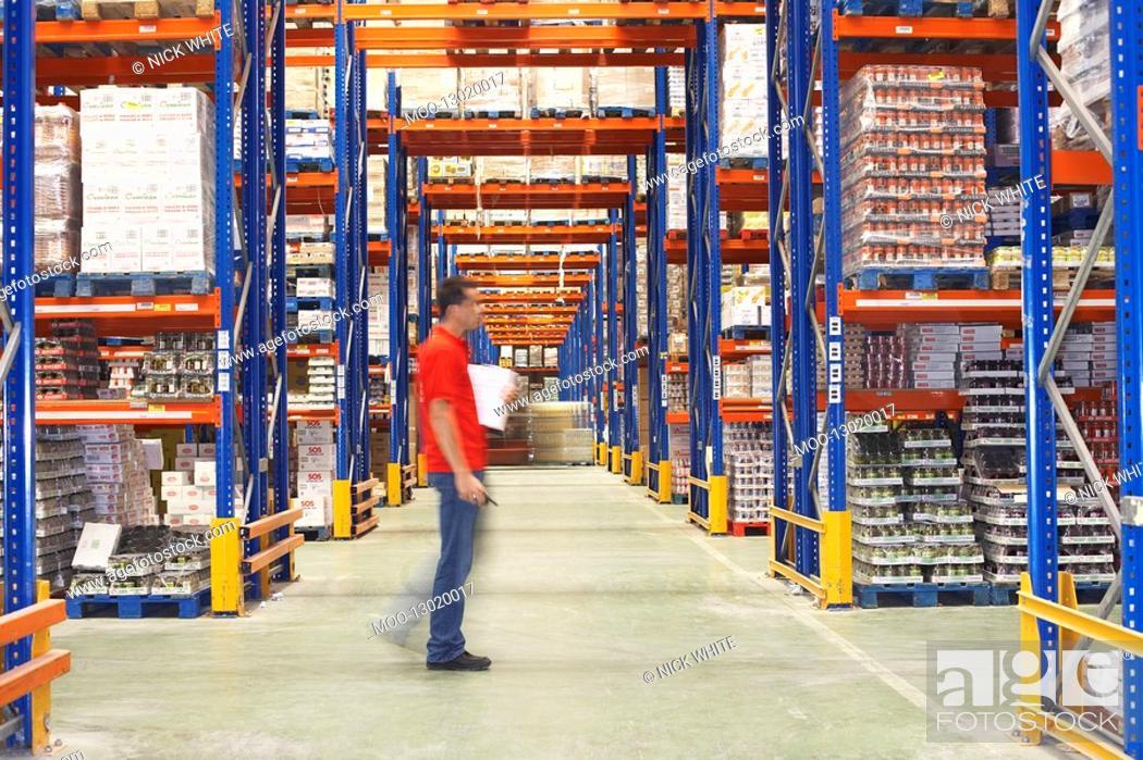 Stock Photo: Man Walking Through Warehouse side view.
