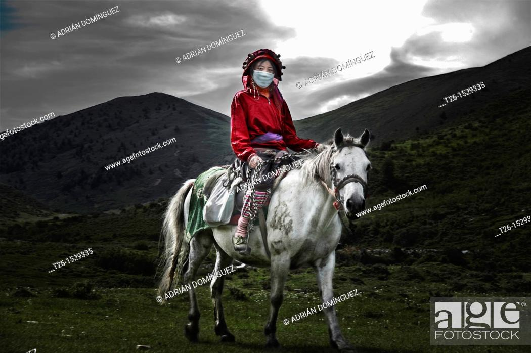 Stock Photo: Tibetan woman ride a horse in the mountain near to Tagong town. China country.