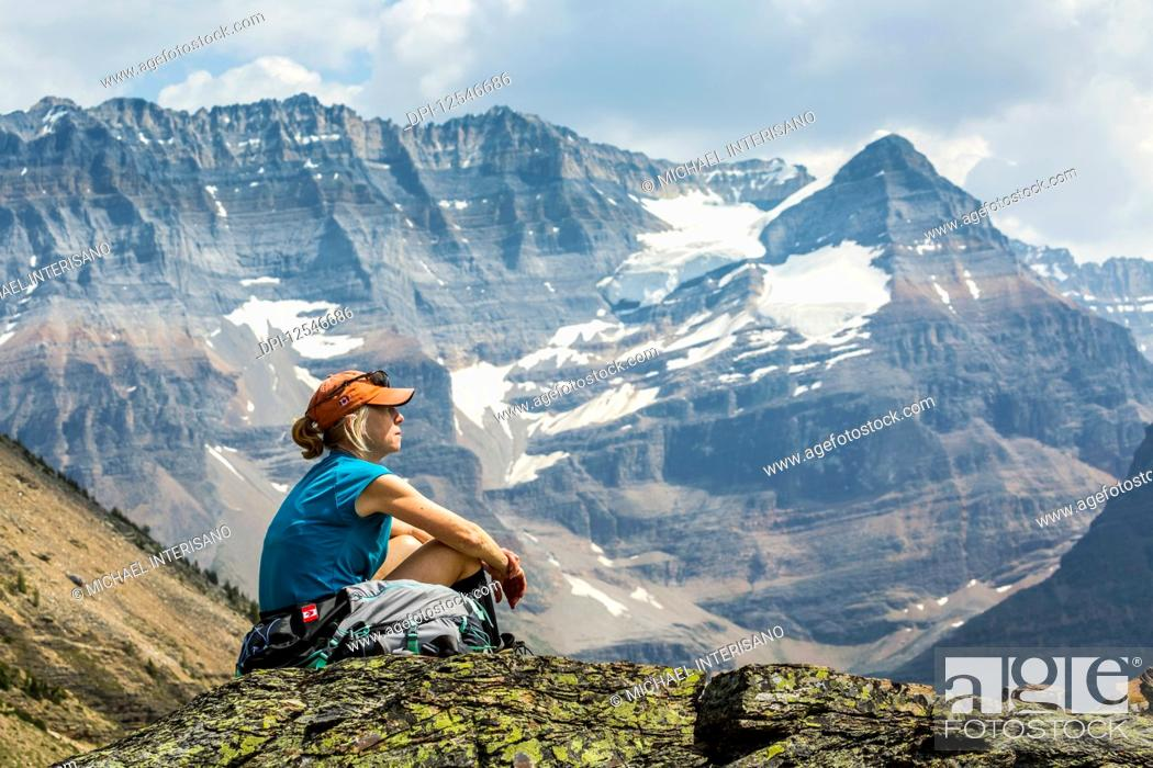 Imagen: Female hiker sitting on a rocky area overlooking mountain vista in the background; British Columbia, Canada.