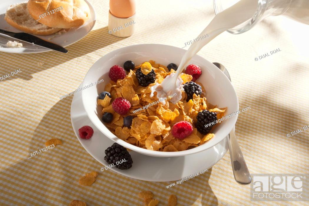 Stock Photo: Milk being poured on a bowl of cornflakes with fruit.