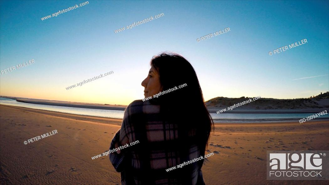 Stock Photo: Rear view of woman wrapped in shawl looking away on Cannon Beach, Oregon, USA.