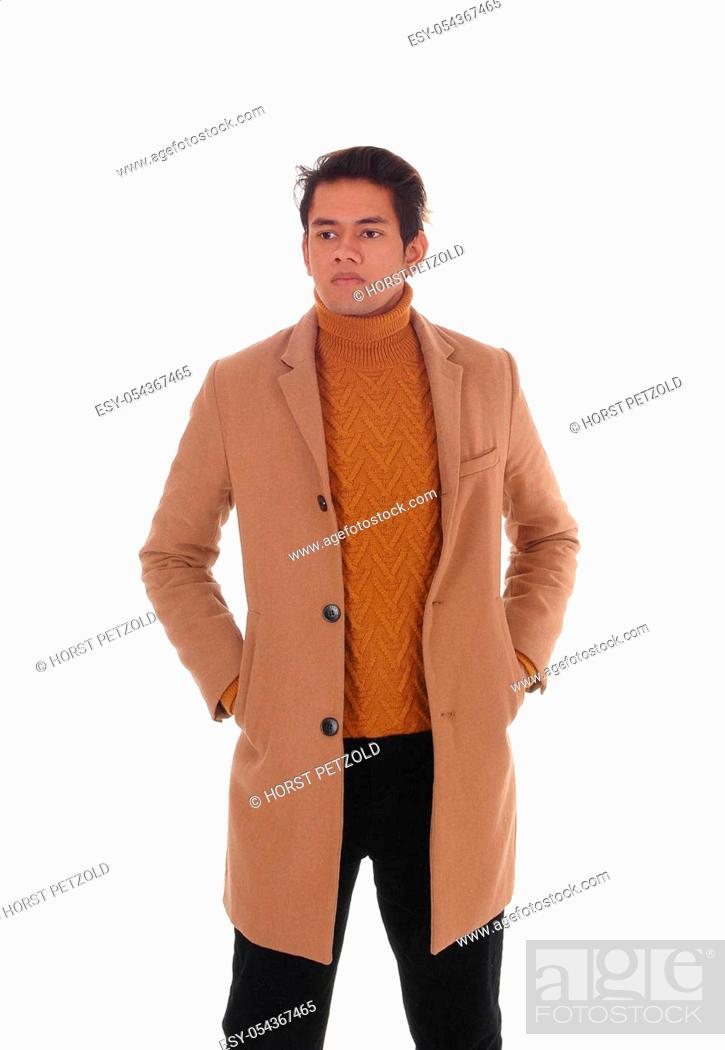Stock Photo: Handsome young man standing in a beige winter coat with his hands.in his pocket, wearing a sweater, isolated for white background.