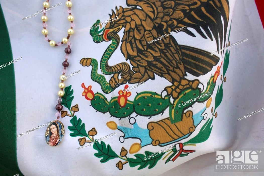 Stock Photo: A rosary with the image of Our Lady of Guadalupe decorates a Mexican flag in Mexico City, December 11, 2010  Hundreds of thousands of Mexican pilgrims converged.