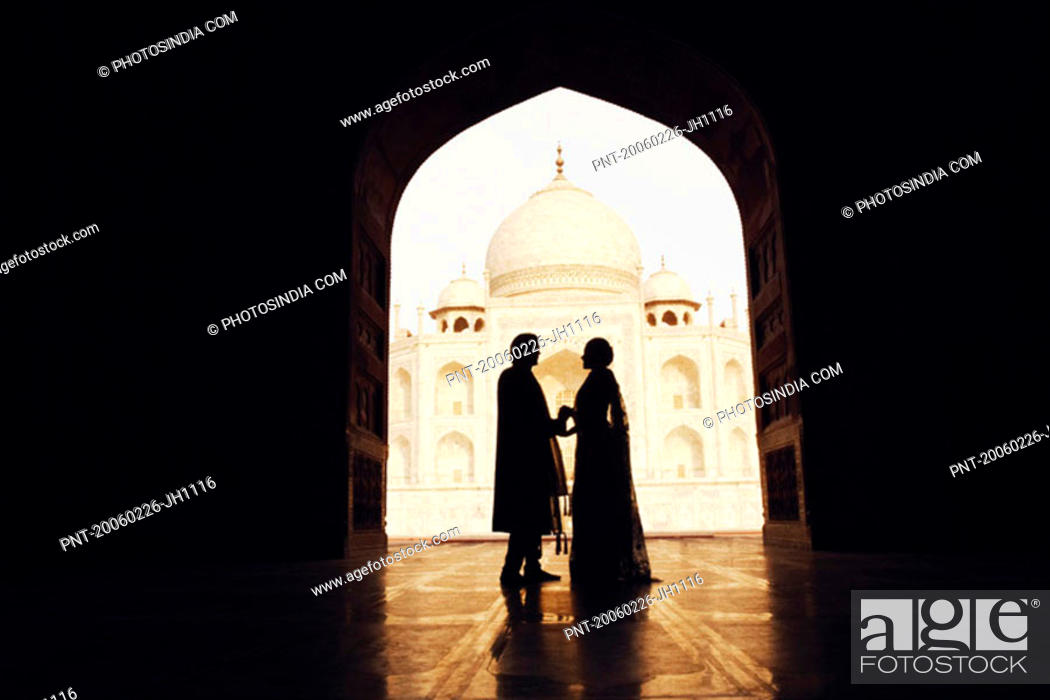 Stock Photo: Silhouette of a couple standing in front of a mausoleum, Taj Mahal, Agra, Uttar Pradesh, India.