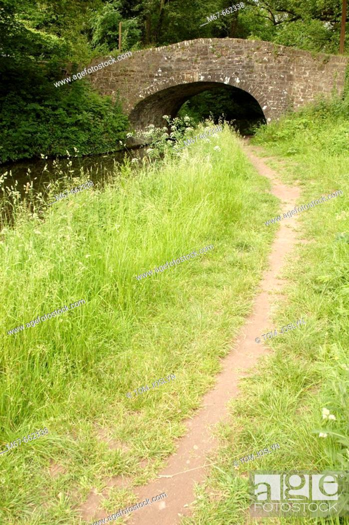 Stock Photo: Footpath leading up to old bridge over canal. Wales, UK.