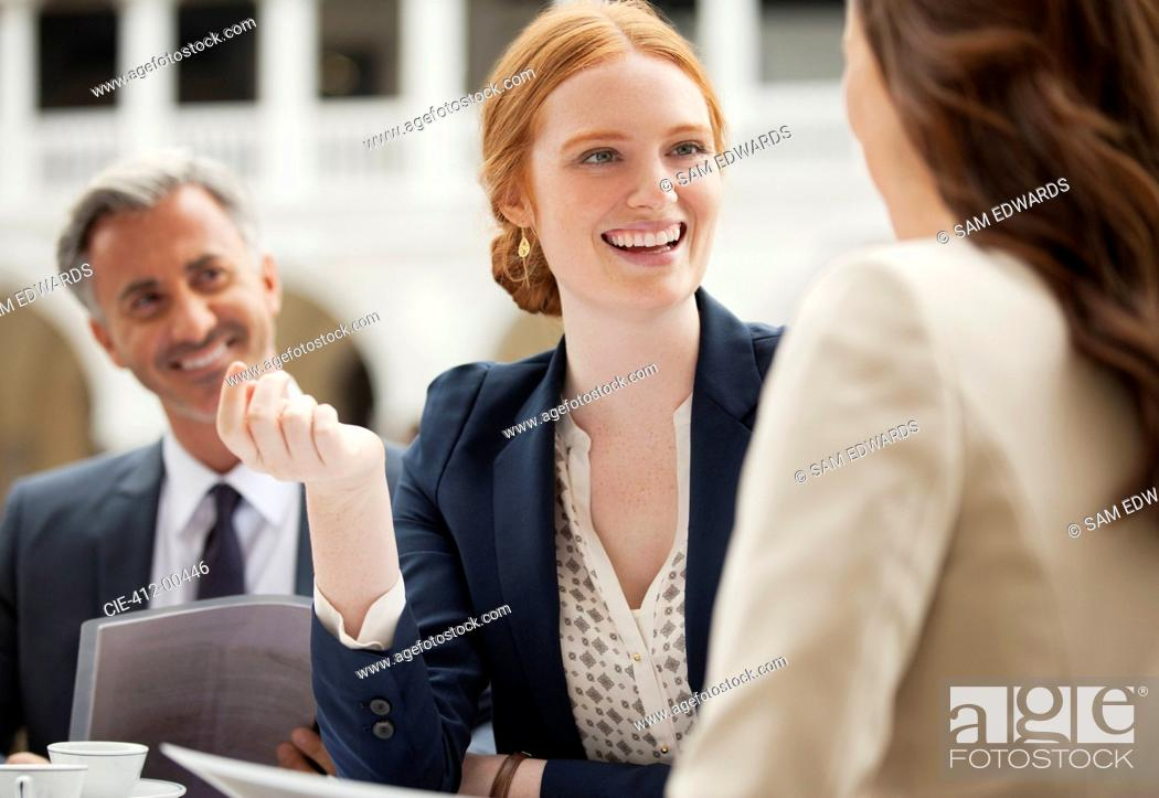 Stock Photo: Smiling business people meeting at sidewalk cafe.