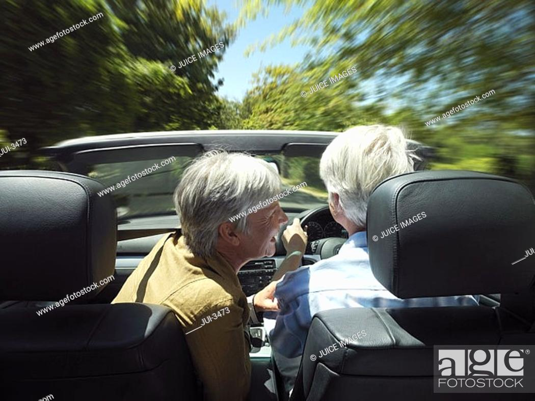 Stock Photo: Senior couple driving in convertible car along country road, woman leaning towards man, rear view.