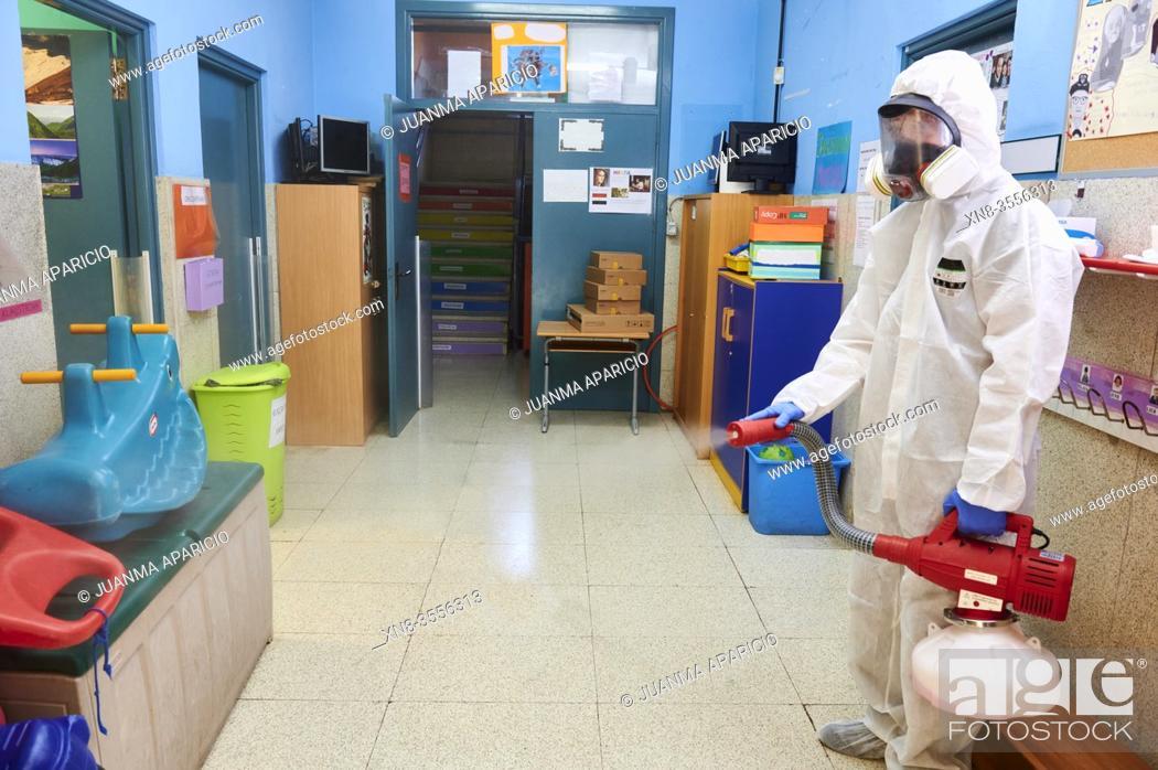 Imagen: Worker in protective suit disinfect interior of the school.