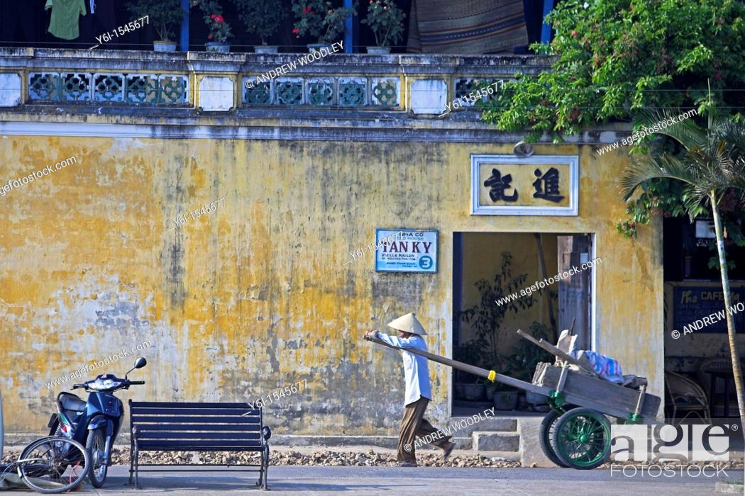 Stock Photo: Man in conical hat pulls hand cart along street Hoi An historic town mid Vietnam.