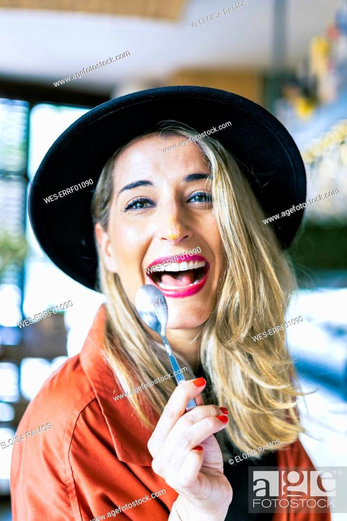 Stock Photo: Portrait of laughing woman with a spoon in a cafe.