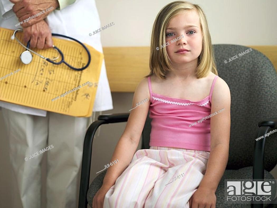 Stock Photo: Blonde girl 6-8 sitting in hospital waiting room beside doctor, portrait.