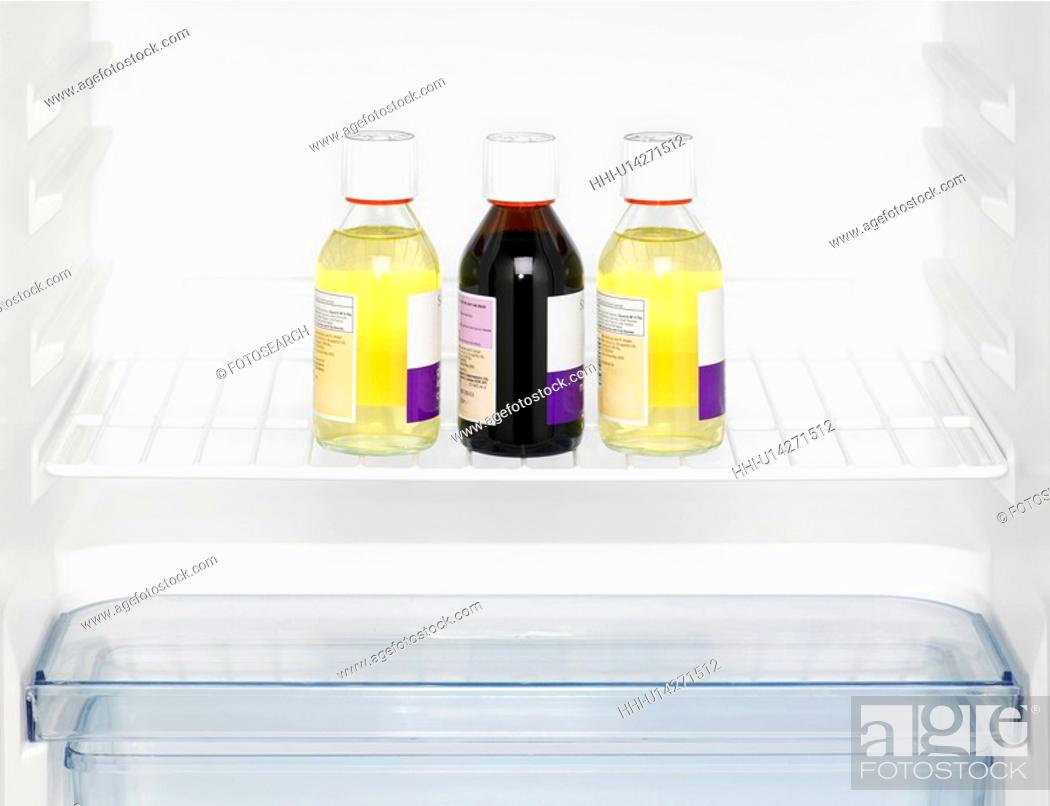 Stock Photo: Three medicine bottles in fridge (close-up).
