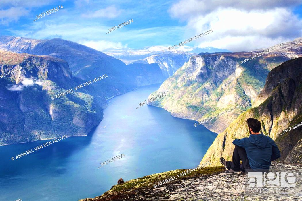 Stock Photo: Man sitting on cliff edge alone enjoying aerial view backpacking lifestyle travel adventure outdoor summer vacations in Norway top of beautiful mountain blue.