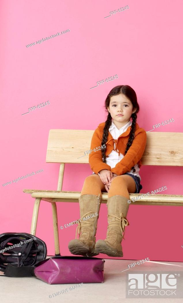 Stock Photo: Girl sitting on a bench.