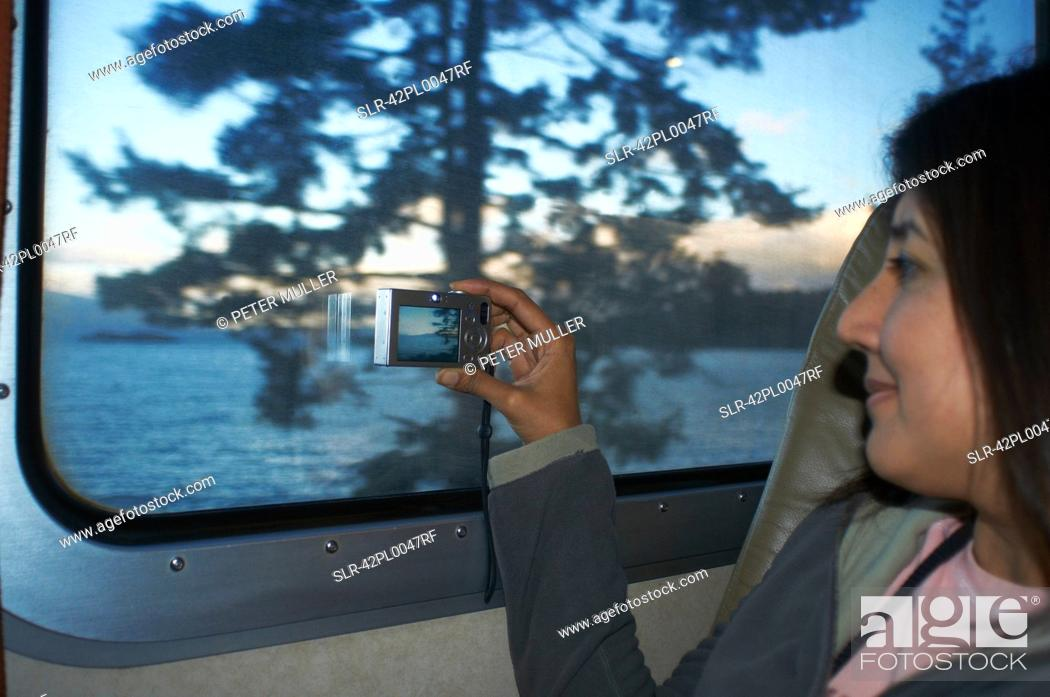 Stock Photo: Woman taking pictures at train window.