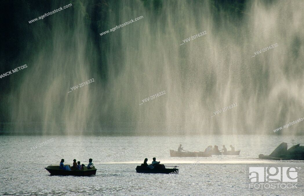 Stock Photo: Tourists are boating on Nakki lake. Mount Abu, India. A water jet is located on the right side. Because of the wind, drops of water are sent to the left.