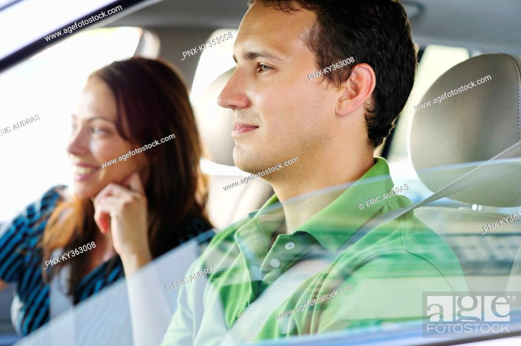 Stock Photo: Happy couple driving a car.