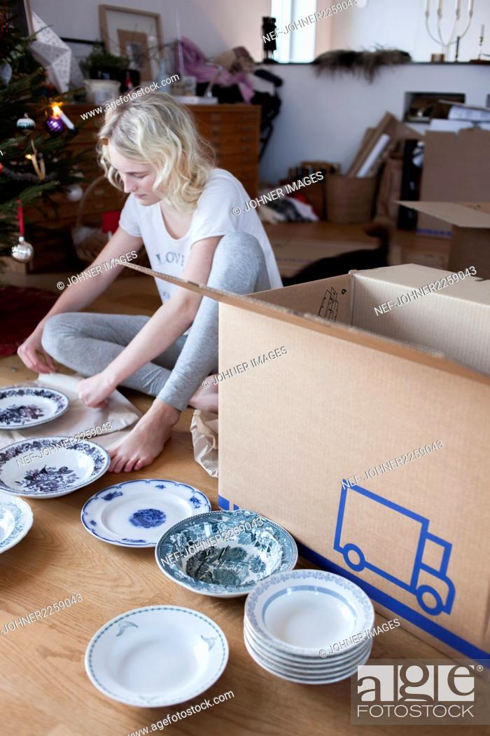 Stock Photo: Teenage girl packing plates into moving box.