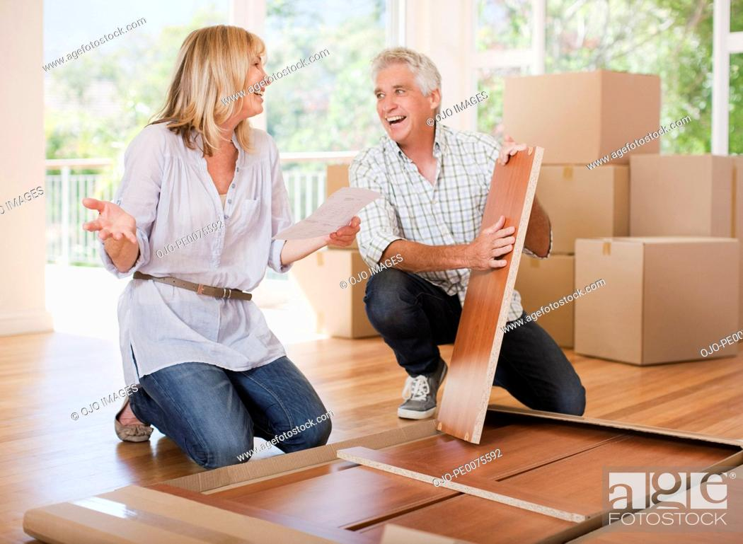 Stock Photo: Couple unpacking boxes in new house.